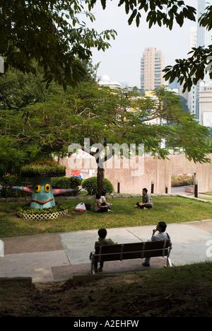 dh Kowloon Park TSIM SHA TSUI HONG KONG Leute entspannt auf Gras- und Bänke im park - Stockfoto