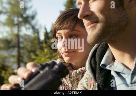 Junges Paar, Mann mit Fernglas - Stockfoto