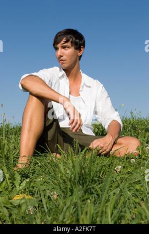 Junger Mann sitzt auf Wiese - Stockfoto