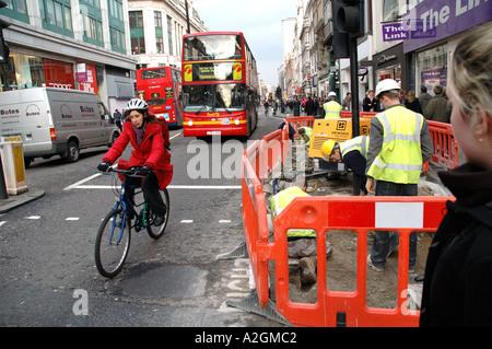 Frau auf dem Fahrrad und Bus vorbei vorübergehender Wartungsarbeiten in der Oxford Street. - Stockfoto