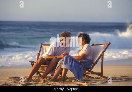 Älteres Paar Hand in Hand und blickte in jeweils anderen Augen als sie sitzen in Klappstühle am Strand - Stockfoto