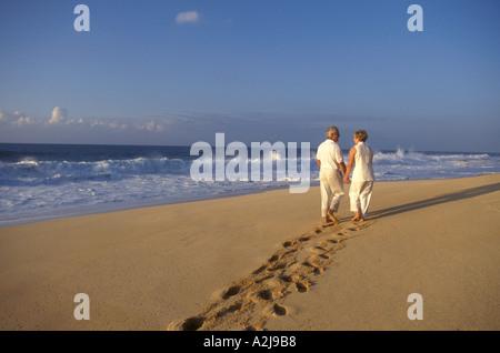 Älteres paar hinterlassen tiefe Spuren im Sand, wie sie zusammen einen leeren Strand zu Fuß und Hand in Hand - Stockfoto