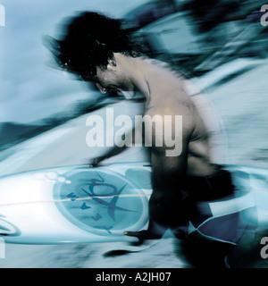 Weißer Mann aus Brasilien Alter 20-25 tragen ein Surfbrett am Strand in Brasilien. - Stockfoto