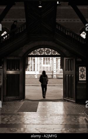 Junge Frau, die zu Fuß durch Durchgang mit einsame Gestalt overhead - Stockfoto