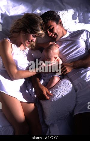 Neue Mutter und Vater im Bett mit ihrem neugeborenen Kind halten und lieben das Baby kuscheln - Stockfoto