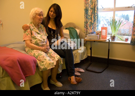 junge Mädchen/Teenager /care Arbeitskraft Besuch sehr alte Dame / ihre Urgroßmutter im Pflegeheim - Stockfoto