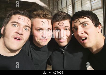 Vier junge Männer mit den Worten Hallo Mom auf Stirn - Stockfoto