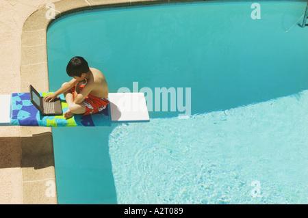 Ein Junge sitzt auf einem Sprungbrett mit seinem laptop - Stockfoto