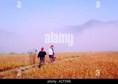 Vater und Sohn Fischer zu Fuß durch ein Feld im Bulkley Tal gehen Sie Angeln in British Columbia Kanada - Stockfoto