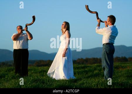 zwei Mann Männer Schofar Spieler weht über Mädchen Frau weibliche Braut im weißen Hochzeit Kleid Deb Debütant auf - Stockfoto