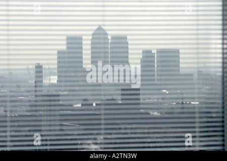 Abstraktes Bild von Canary Wharf Gebäuden durch Jalousien Bürogebäudes in Stadt von London EC3 E14 England UK - Stockfoto