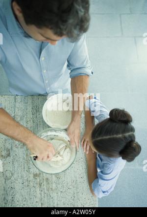 Mädchen beobachten, wie Vater mischt Teig, erhöhte Ansicht - Stockfoto