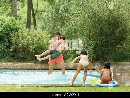 Vater mit Kindern im Pool Spielen - Stockfoto