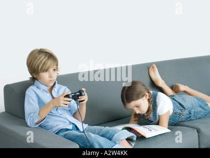 Junge sitzt auf Sofa, Holding-Joystick, Mädchen neben ihm lesen - Stockfoto
