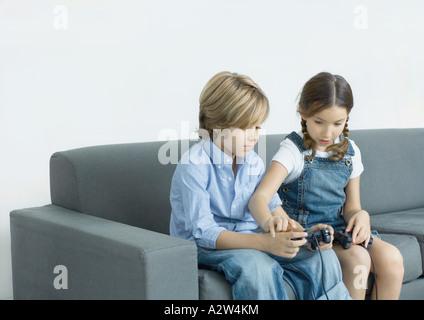 Mädchen helfen jungen mit joystick - Stockfoto