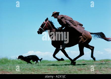 Outdoor-Seitenansicht von einem jungen Mann in einem langen Mantel und Hut auf einem Pferd im Galopp mit seinem - Stockfoto