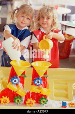 Zwei Schulmädchen spielen drinnen mit bunten Plastik Wasser Aktivität Spielzeug. - Stockfoto