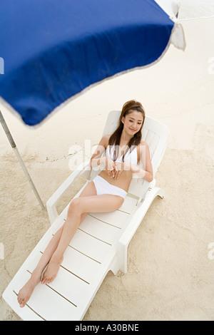 Frau im Liegestuhl am Strand - Stockfoto
