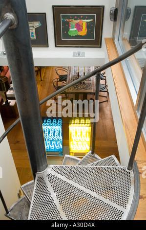Ansicht von oben der Wendeltreppe nach unten in den offenen Wohnbereich mit Neon-Licht-Installation im Penthouse - Stockfoto