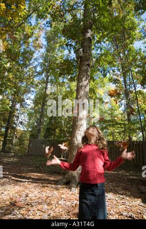 Mädchen spielen mit Blättern im Herbst - Stockfoto