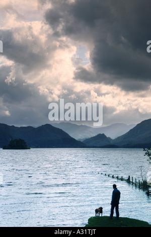 ein Mann und sein Hund Stand am Ufer des Derwent Water im Lake District - Stockfoto
