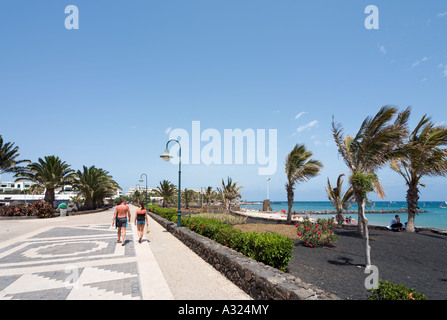Paar zu Fuß entlang der Promenade am Strand von Playa de Las Cucharas, Costa Teguise, Lanzarote, Kanarische Inseln, - Stockfoto