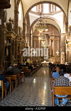 Mexiko San Miguel de Allende Mann im karierten Hemd zurücklehnen in Zeile während der Trauerfeier in römisch-katholische - Stockfoto