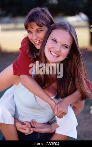 ältere Schwester, die jüngere Schwester Huckepack Fahrt geben - Stockfoto