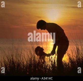 Silhouette von Vater und Kind stehen in der Nähe von dem Rand des Ozeans wie die Sonne im Hintergrund - Stockfoto