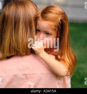 Ein junges Mädchen mit roten Haaren ihre Daumenlutschen und über ihre Mutter Schulter schaut, wie sie ihre Mutter - Stockfoto