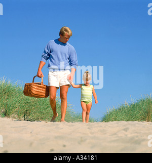 Vater und Tochter zu Fuß über eine Düne am Strand während Sie Hand in Hand des Vaters trägt einen Picknick-Korb - Stockfoto