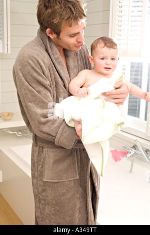 Junger Mann im Bademantel mit Baby im Badezimmer - Stockfoto