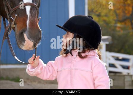 Drei Jahre altes Mädchen liebevoll mit Blick auf ihr Pferd Stanhope Ställe Huntington NY - Stockfoto