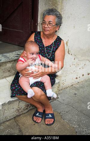 Frau sitzt und hält ihr Enkelkind, Sancti Spiritus, Provinz Sancti Spiritus, Kuba - Stockfoto