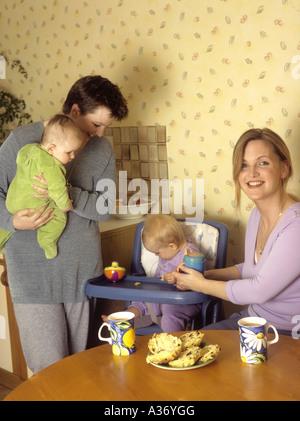 Frauen mit ihren Babys, plaudern und lachen zusammen in einer Küche - Stockfoto