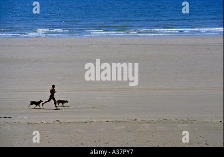 Mann läuft am Strand mit zwei Hunden Rest Bay Porthcawl Wales UK - Stockfoto