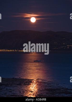 MOON RISE über MENAI STRAIT mit Vollmond über dem Tal y Fan von Beaumaris Anglesey North Wales UK - Stockfoto
