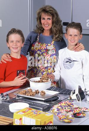 Mutter und Söhne zu Hause zusammen Kekse backen - Stockfoto