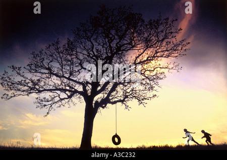 Silhouette der beiden Kinder laufen an Baum mit Reifen Schaukel Sonnenuntergang - Stockfoto