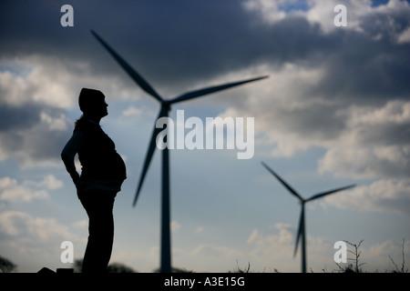 werdende schwangere Frau sucht für eine grünere Zukunft an einem Windpark, Windkraftanlagen im Hintergrund mit dramatischer - Stockfoto