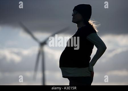 werdende schwangere Frau sucht für eine grünere Zukunft an einem Windpark, Windkraftanlagen im Hintergrund. in Devon - Stockfoto