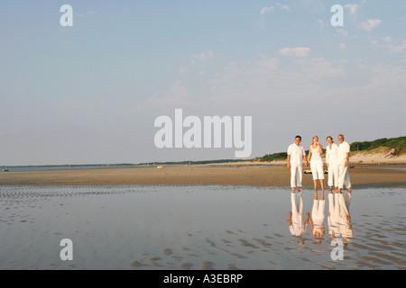 Älteres paar stehend mit einer Mitte erwachsenen Frau und einem reifen Mann am Strand - Stockfoto