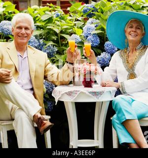 Porträt von einem reifen Mann und eine ältere Frau beisammen sitzen und halten Gläser Saft - Stockfoto
