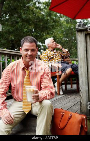 Porträt eines Geschäftsmannes hält einen Becher Milchshake und lächelnd - Stockfoto
