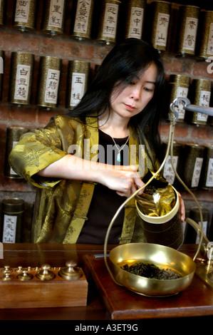 """Paris Frankreich, chinesischen Tee Spezialist"""" Yu hui Tseng-Weighing schwarzer Tee auf der Skala in der Teestube - Stockfoto"""