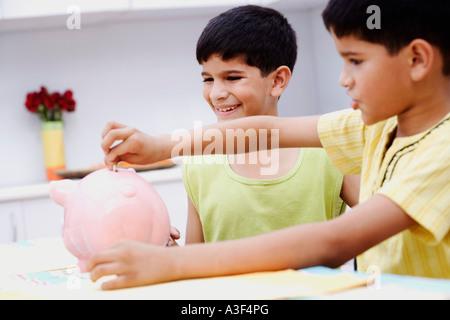 Junge einfügen eine Banknote in ein Sparschwein mit seinem Bruder neben ihm lächelnd - Stockfoto