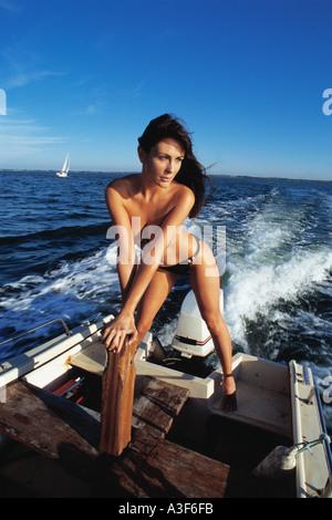 Mädchen im Bikini stehen auf Geschwindigkeit Boot Spray hinter - Stockfoto