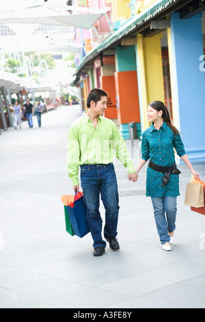 Junge Paare, die mit Einkaufstüten - Stockfoto