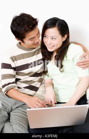 Nahaufnahme eines Mitte erwachsenen Menschen umarmt eine junge Frau mit einem laptop - Stockfoto