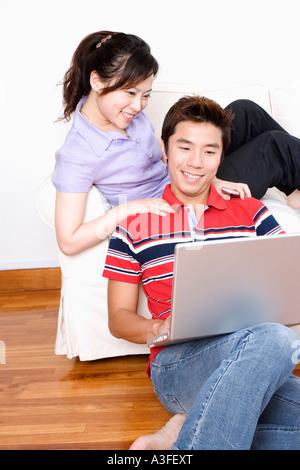 Junge Frau sitzt auf einer Couch mit einem Mitte erwachsener Mann mit einem laptop - Stockfoto